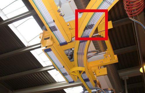 Rails électriques pour l'alimentation en puissance et contrôle d'un convoyeur aérien sur monorail HEA avec vu d'un aiguillage.