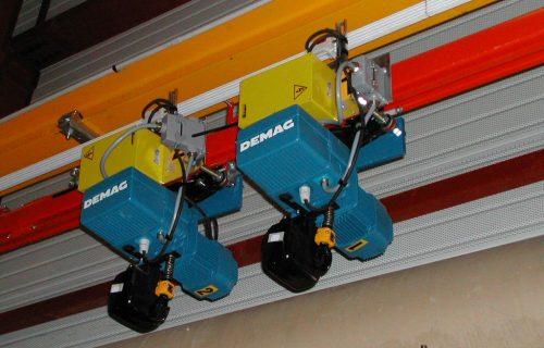 Rails électriques pour l'alimentation de plusieurs palans le long d'un chemin de roulement cintré.