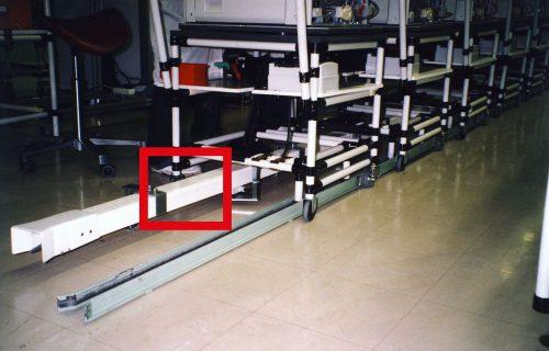 Rails électriques avec entrée et sortie des chariots collecteurs pour l'alimentation de tables roulantes sur une chaîne de contrôle.