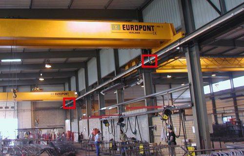 Rails électriques pour l'alimentation de ponts roulants dans un local de fabrication d'armatures métalliques.