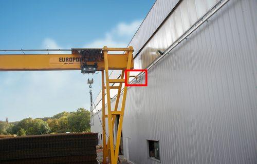 Rails électriques pour l'alimentation d'un portique en service extérieur, exposés aux intempéries.