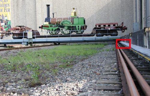 Rails électriques pour l'alimentation d'un transbordeur pour locomotives à vapeur à l'entrée dans un musée des chemins de fer.