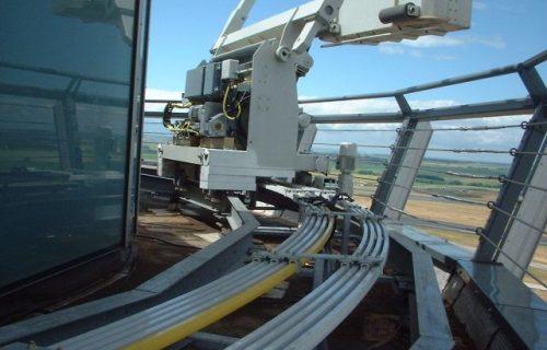 Rails électriques pour l'alimentation et l'asservissement d'une nacelle évoluant sur une tour de contrôle d'aéroport (Roissy), en service extérieur.